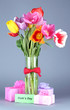 Beautiful tulips in bouquet with gifts and note