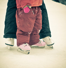 Child and parent feet on skates