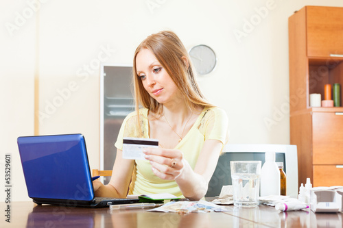 long-haired woman buying drugs online with laptop