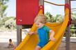 Little toddler boy sitting on playground
