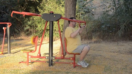 Fat man on an exercise pull down trainer