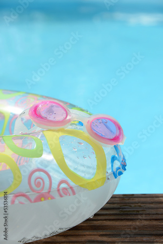 child buoy, goggles and swimming pool background