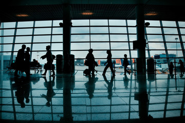 Silhouettes of people with luggage walking at airport