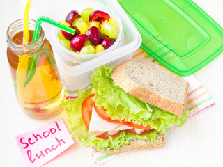 Bento lunch for child in school, box with sandwich, fruit, juice
