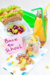 School lunch for child, box with sandwich, nuts, fruit, juice