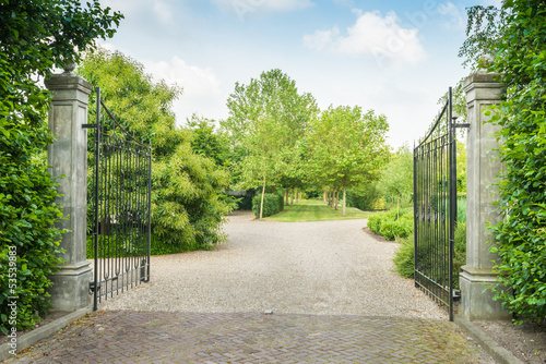 Opened black wrought iron gate of a large estate - 53539883