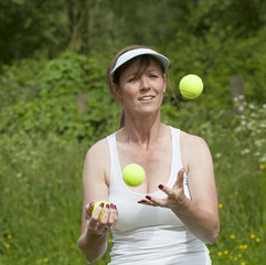 Woman juggling green tennis balls