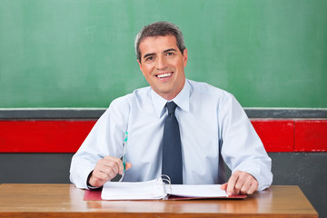 Happy Male Teacher With Pen And Binder Sitting At Desk