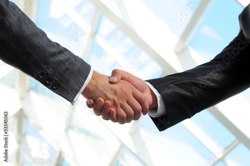 Business man giving a handshake to close the deal