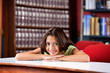 Happy Schoolgirl Resting Chin On Hands At Table In Library