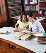 Schoolgirl Showing Book To Classmate In Library