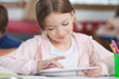 Schoolgirl Smiling While Using Tablet At Desk