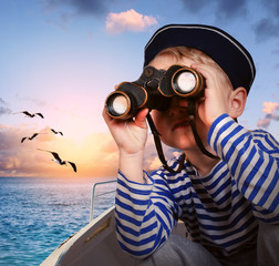 Sailor boy with binoculars in the boat