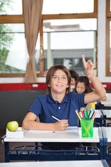 Happy Schoolboy Raising Hand In Classroom