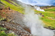 Woman hiking in geothermal landscape along geysers, Iceland