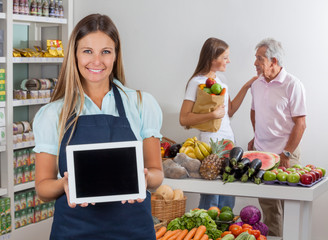 Saleswoman Displaying Tablet With Customers In Background