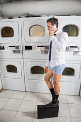 Businessman Using Mobile Phone In Laundry