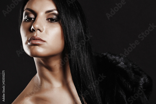Beautiful brunette woman. black fur