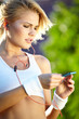 Beautiful woman during fitness on city is listen to the music