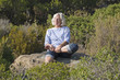 zen senior woman enjoying quietness and exercising outside