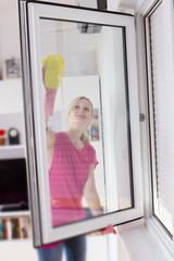 Housewife with protective glove washing the window glass