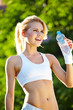 Portrait of cheerful young attractive woman drinking water, outd