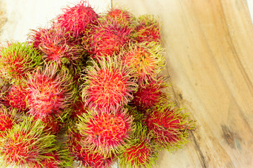 Tropical fruit, rambutan on wood background