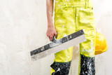 Construction worker with putty knife over obsolete background poster