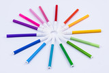 Colourful markers on white background.