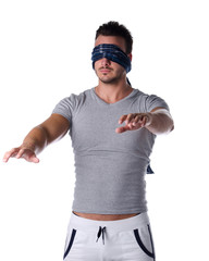 Blindfolded young man feeling his way in the dark