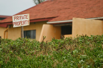 Private property sign with a residential house in the background
