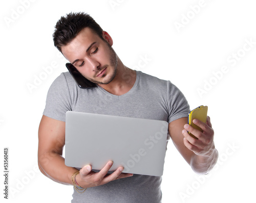 Overwhelmed by technology. Guy with 2 cell phones and a computer