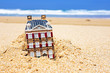 House disappearing in the sand. Concept for real estate in crisi
