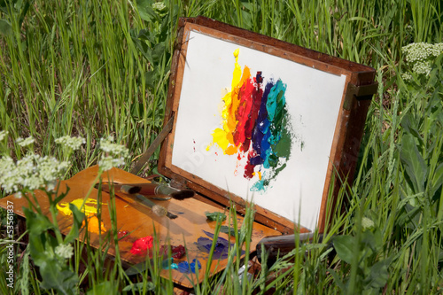 painter case on grass with palette and artistic tools