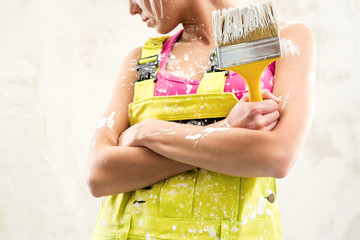 Female in coverall holding paint brush over obsolete white wall