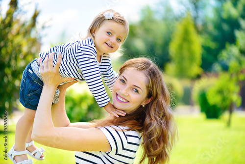 Young mother and cute daughter with blue eyes playing at park