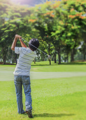 Male golf player teeing-off golf ball
