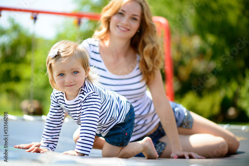 Young mother and little daughter playing at playground
