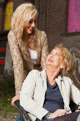 Blonde mother and daughter portrait in urban scenery.