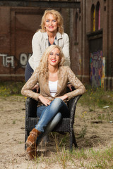 Pretty blonde fashion mother and daughter outdoor in urban envir