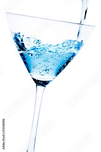 filling a glass with blue cocktail tilted and bubbles