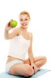 Young woman doing yoga and hold apple