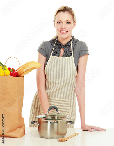 Woman in apron standing near table with grocery bag