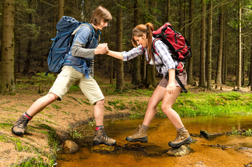 Hiker boy help trekking girl crossing creek