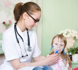Doctor holding inhaler mask for kid breathing