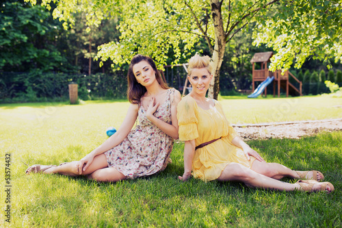 Two romantic ladies sitting on flower meadow