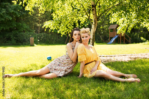 Two attractive women resting on the flower meadow