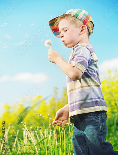 Young cheerful boy playing blow-ball