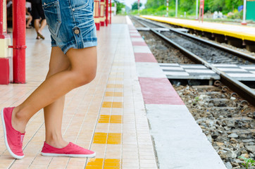 Girl waiting for the Train behind yellow line
