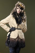 beautiful fashion woman in fur coat with hat posing